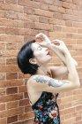 Чувственная брюнетка женщина в узорчатом платье, стоящая рядом с кирпичной стеной — стоковое фото