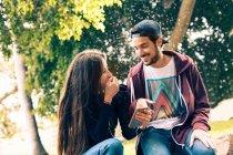 Rire jeune couple assis avec smartphone dans le parc — Photo de stock