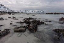 Rocce lisce in corso d'acqua con montagne innevate sullo sfondo — Foto stock