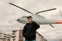 Hombre joven guapo permanente monumento de helicóptero en la ciudad y hablar por teléfono inteligente - foto de stock