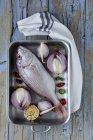 Sargo do mar cru na assadeira com legumes na mesa de madeira — Fotografia de Stock