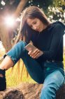 Young woman sitting on rock and using smartphone in park — Stock Photo