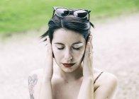 Молодая хипстерша сидит на улице и закрывает уши руками — стоковое фото