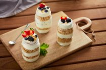 Glass jars with granola and yogurt on wooden board — Stock Photo