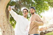 Sonriente feliz macho amigos tomando selfie con smartphone en sunny park - foto de stock
