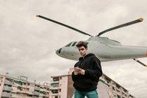 Atractivo joven parado en monumento de helicóptero en la ciudad y el uso de smartphone - foto de stock