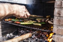 Close-up of man hand doing barbecue with vegetables and meat — Stock Photo