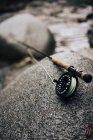 Gros plan de la canne à pêche sur rocher lisse sur le rivage dans la nature — Photo de stock