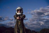 Astronauta hembra tomando selfie con teléfono móvil contra el cielo nocturno en la naturaleza - foto de stock