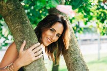 Cheerful stylish woman standing under tree embracing trunk and smiling at camera in park — Stock Photo