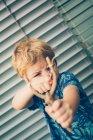 Menino loiro em t-shirt jogando com estilingue contra persianas — Fotografia de Stock