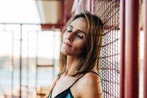 Femme calme avec les yeux fermés appuyé sur une clôture métallique à l'extérieur — Photo de stock