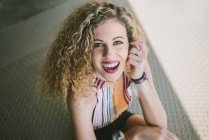 Ritratto di giovane donna riccia con labbra luminose sorridenti all'aperto — Foto stock