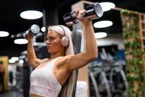Jeune femme blonde en haut de sport avec casque faisant de l'exercice avec des haltères en fer sur l'équipement de gymnastique — Photo de stock