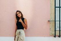 Affascinante donna bruna in abito alla moda appoggiata al muro sulla strada e guardando la fotocamera — Foto stock