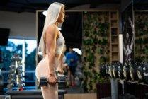 Спортсменка занимается спортом с гантелями в спортзале — стоковое фото