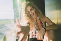 Jovem mulher encaracolado sentado em sol brilhante e estendendo a mão borrada com sorriso — Fotografia de Stock