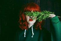 Giovane donna dai capelli rossi che copre gli occhi con ramoscello di abete verde su sfondo nero — Foto stock