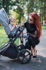 Giovane madre guardando la bambina nel passeggino nel parco soleggiato — Foto stock
