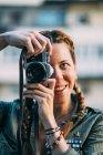 Ritratto di ragazza rossa sorridente con trecce scattare foto con fotocamera vintage — Foto stock