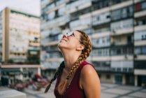 Усміхаючись руда дівчина з косами і сонцезахисні окуляри, ходьба в місті — стокове фото