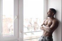 Бічний вид дорослого чорного чоловіка, який користується телефоном, стоячи проти вікна в м