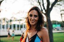 Porträt einer lächelnden brünetten Frau im Stadtpark — Stockfoto