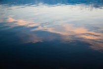 Calm water of lake with reflection of sunset sky on surface — Stock Photo