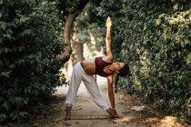 Barefoot woman doing yoga on path in autumn garden — Stock Photo