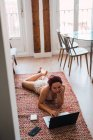 Young woman lying on floor at home and using laptop — Stock Photo