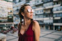 Стильний руда дівчина з косами і сонцезахисні окуляри, стоячи в місті — стокове фото