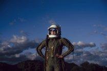 Confiada mujer astronauta feliz de pie en la naturaleza por la noche - foto de stock