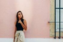 Affascinante donna bruna in abito alla moda appoggiata al muro sulla strada e guardando altrove — Foto stock