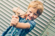 Blonde little boy in t-shirt playing with slingshot against shutters — Stock Photo