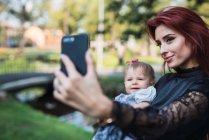 Giovane madre elegante scattare selfie con allegro bambino nel parco — Foto stock