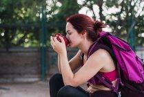 Молодая спортсменка с рюкзаком сидит на улице и пьет кофе — стоковое фото