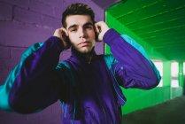 Ritratto di un giovane in abbigliamento sportivo che ascolta musica contro un muro colorato — Foto stock