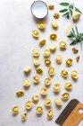 Tortellini fatti a mano su fondo bianco con foglie di erbe e farina — Foto stock