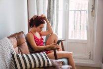 Mujer joven en traje de baño rojo sentada en sillón en la habitación y usando teléfono inteligente - foto de stock