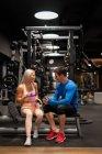Атлетичный мужчина и женщина в спортивной одежде сидят в спортзале и смеются — стоковое фото