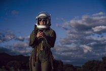 Astronauta sonriente en gafas de sol sosteniendo el teléfono móvil contra el cielo nocturno - foto de stock