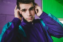 Portrait of young man in sportswear listening to music against colorful wall — Stock Photo