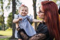Женщина держит взволнованную девочку в парке — стоковое фото
