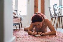 Женщина в нижнем белье лежит на полу и пишет в блокноте — стоковое фото