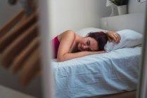 Молодая расслабленная женщина лежит на кровати с закрытыми глазами — стоковое фото