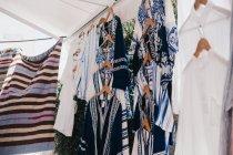 Diferentes túnicas tradicionais em cabides de pano no mercado de rua, Mykonos, Grécia — Fotografia de Stock