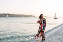 Зміст жінка в давно барвисті сукні, ходьба на набережній кругляком на заході проти морський пейзаж — стокове фото