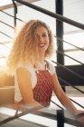 Портрет усміхнений молодої жінки фігурні сидять на сходах у sunshine — стокове фото