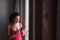 Молодая улыбающаяся женщина наклоняется к окну с помощью мобильного телефона — стоковое фото