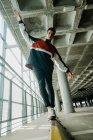Молодой красивый мужчина в спортивной куртке ходит по железным рельсам в просторном здании с колоннами — стоковое фото
